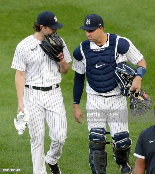 Pitcher Gerrit Cole and catcher Gary Sanchez of the New York Yankees talk as they walk in from the bullpen to start in an MLB baseball game against...
