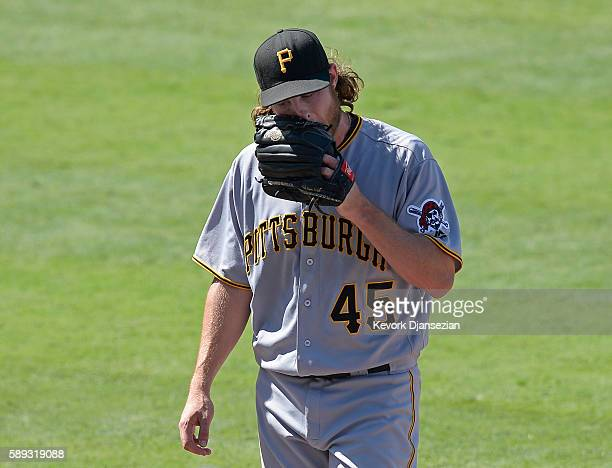 Pitcher Gerrit Cole of the Pittsburgh Pirates walks to the dugout after getting yanked out of the baseball game after giving up two runs to the Los...