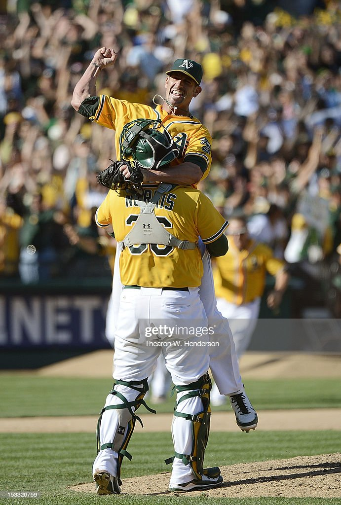Pitcher Grant Balfour #50 of the Oakland Athletics jumps into the arms of catcher Derek Norris #36 celebrating defeating the Texas Rangers 12 to 5 and capturing the American League West title at O.co Coliseum on October 3, 2012 in Oakland, California.