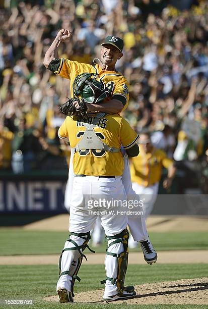 Pitcher Grant Balfour of the Oakland Athletics jumps into the arms of catcher Derek Norris celebrating defeating the Texas Rangers 12 to 5 and...