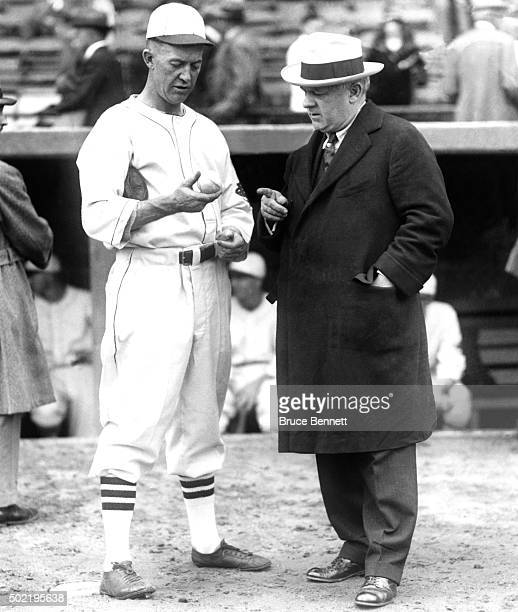 Pitcher Grover Cleveland Alexander of the St Louis Cardinals shows manager John McGraw of the New York Giants a baseball before a game circa 1926 at...