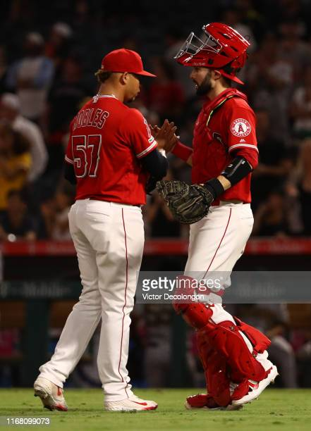 Pitcher Hansel Robles and catcher Anthony Bemboom of the Los Angeles Angels shake hands after their 74 win against the Pittsburgh Pirates in their...