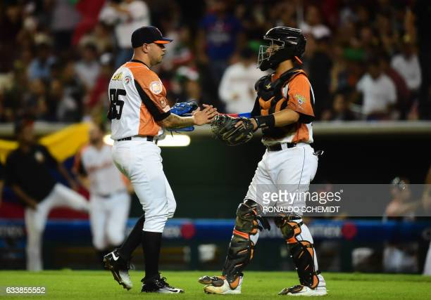 Pitcher Hassan Pena and catcher Francisco Arcia of Aguilas del Zulia from Venezuela celebrate victory over Alazanes de Granma from Cuba following...