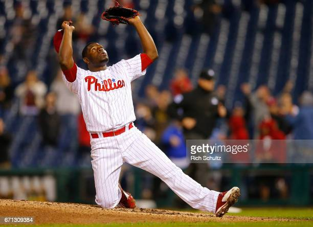 Pitcher Hector Neris of the Philadelphia Phillies drops to a knee and gestures skyward after getting the final out against the Atlanta Braves during...