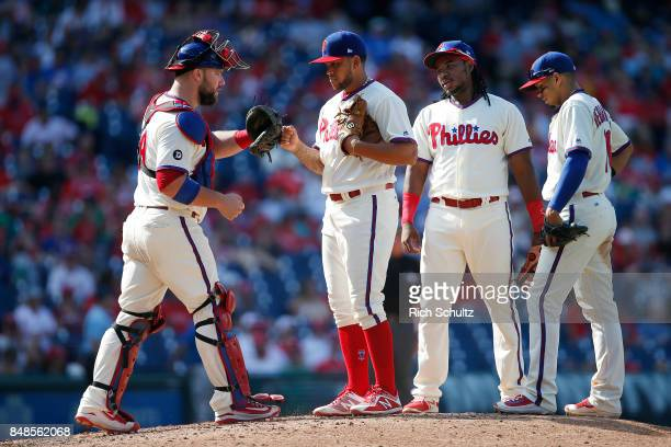 Pitcher Henderson Alvarez of the Philadelphia Phillies gets a fist bump from catcher Cameron Rupp as teammates Maikel Franco and JP Crawford before...