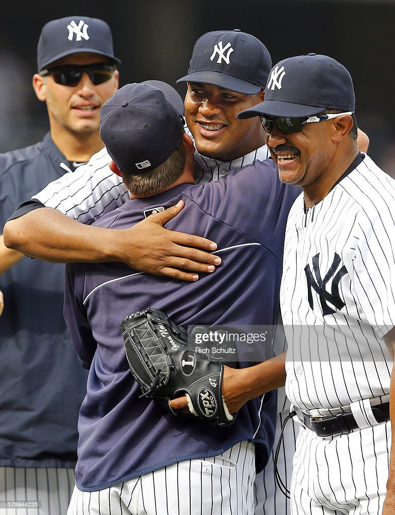 Pitcher Ivan Nova #47 gets a hug from batting coach Kevin Long #54 as pitcher Andy Pettitte #46 and bench coach Tony Pena #56 look on after Nova throw a complete game, three hit shutout against the Baltimore Orioles in a MLB baseball game at Yankee Stadium on August 31, 2013 in the Bronx borough of New York City. The Yankees defeated the Orioles 2-0.