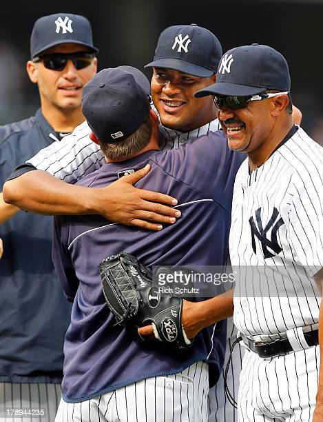 Pitcher Ivan Nova gets a hug from batting coach Kevin Long as pitcher Andy Pettitte and bench coach Tony Pena look on after Nova throw a complete...