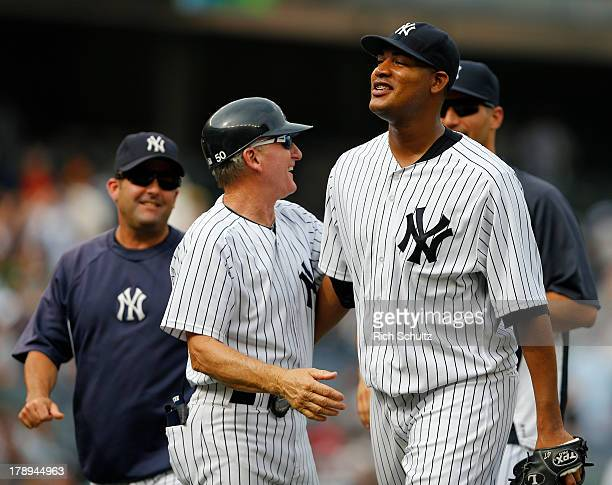 Pitcher Ivan Nova walks off the field with first base coach Mick Kelleher after throwing a complete game three hit shutout against the Baltimore...