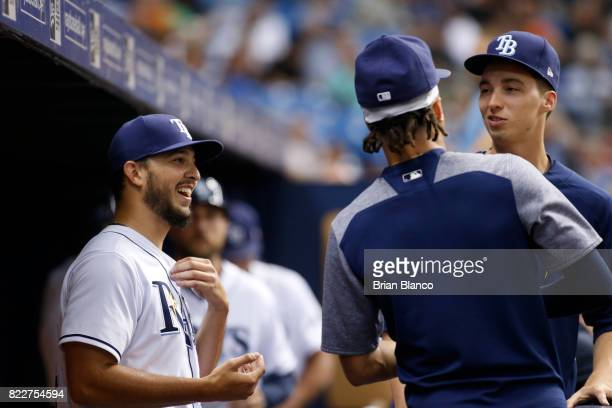 Pitcher Jacob Faria of the Tampa Bay Rays left speaks with teammates and follow pitcher Chris Archer center and Blake Snell in the dugout after being...