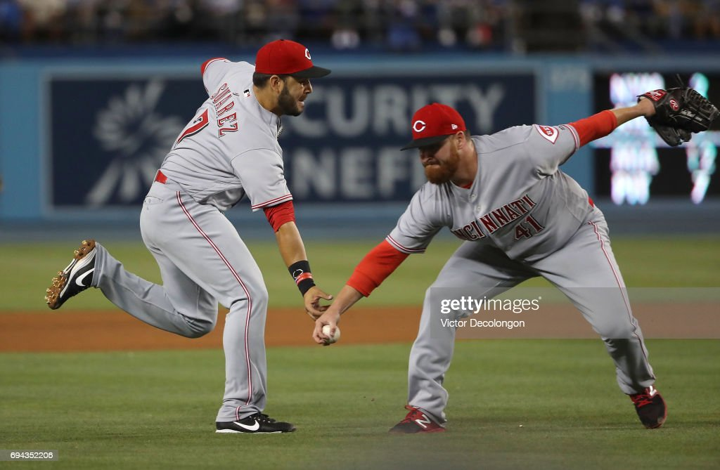 Pitcher Jake Buchanan #41 and Eugenio Suarez #7 of the Cincinnati Reds both go for the infield groundball during the third inning of their MLB game against the Los Angeles Dodgers at Dodger Stadium on June 9, 2017 in Los Angeles, California. Buchanan fielded the ball and made an error throwing to first base.
