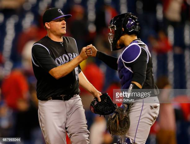 Pitcher Jake McGee of the Colorado Rockies is congratulated by catcher Tony Wolters after getting the final out and defeating the Philadelphia...