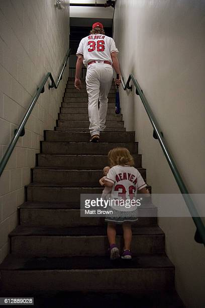 Pitcher Jered Weaver of the Los Angeles Angels of Anaheim and his daughter Josie Weaver head to the clubhouse before the game against the Houston...
