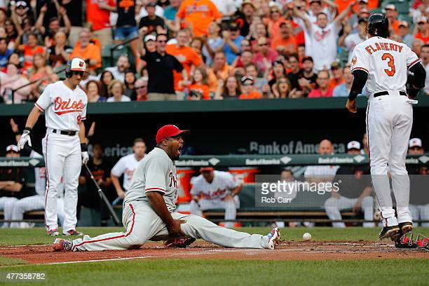 Pitcher Jerome Williams of the Philadelphia Phillies reacts after being injured trying to tag out Ryan Flaherty of the Baltimore Orioles at home...