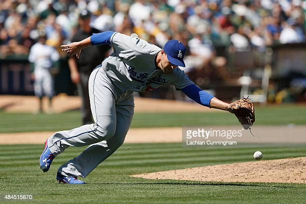 Pitcher Jim Johnson of the Los Angeles Dodgers is unable to field a bunt off the bat of Billy Burns of the Oakland Athletics in the eighth inning of...