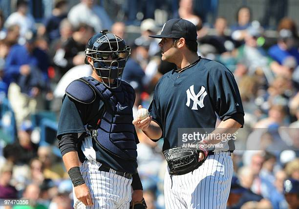 Pitcher Joba Chamberlain of the New York Yankees talks with catcher Francisco Cervelli after taking the mound in relief against the Tampa Bay Rays...