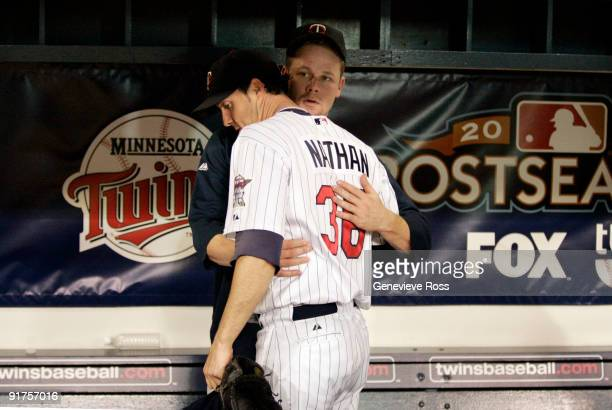 Pitcher Joe Nathan of the Minnesota Twins is comforted by teammate Justin Morneau after being defeated by the New York Yankees in Game Three of the...