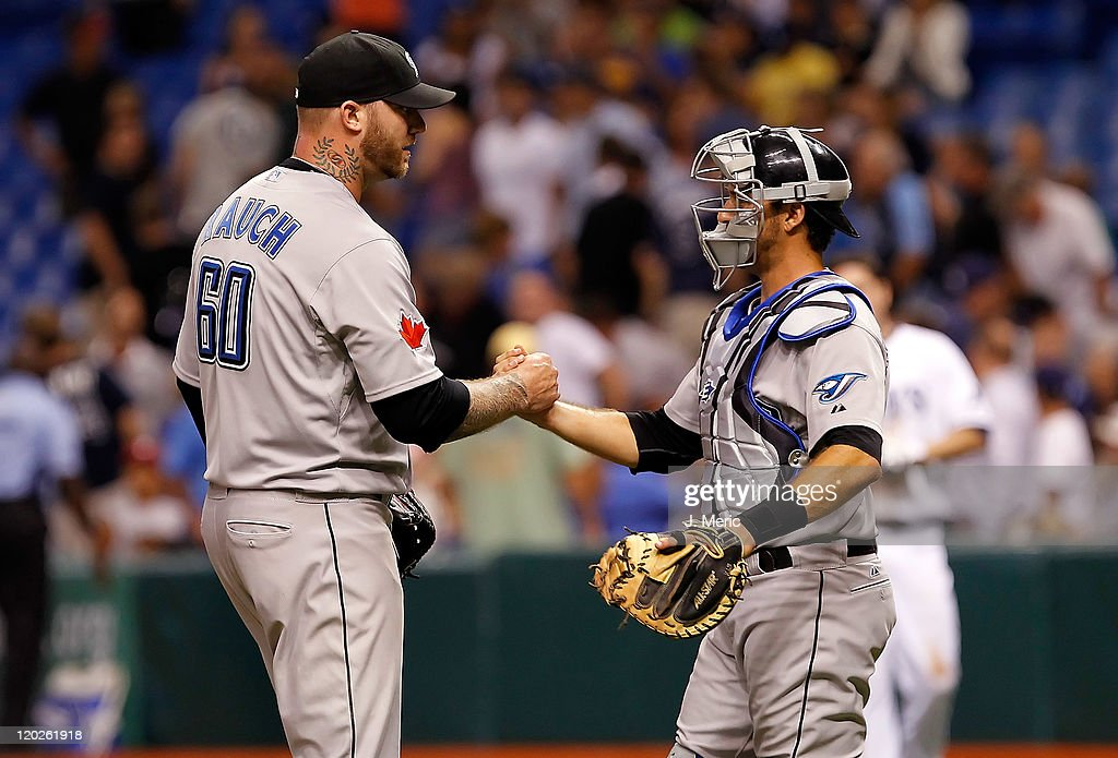 Pitcher Jon Rauch #60 of the Toronto Blue Jays is congratulated by catcher J.P. Arencibia #9 after his save against the Tampa Bay Rays at Tropicana Field on August 2, 2011 in St. Petersburg, Florida.