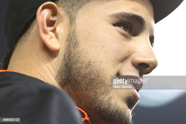 Pitcher Jose Fernandez of the Miami Marlins watches from the bench as his team plays against the New york Mets during the second inning at Marlins...