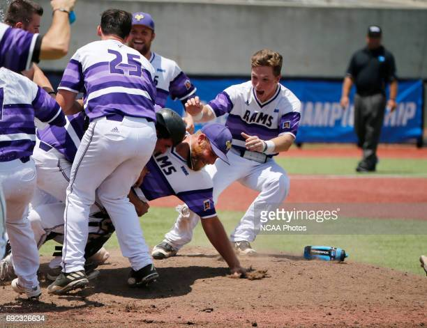 Pitcher Josh McClain of West Chester University is swarmed by teammates after they defeated UC San Diego during the Division II Men's Baseball...