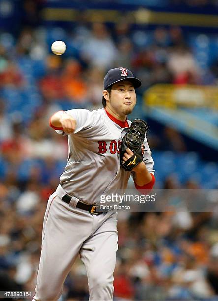 Pitcher Junichi Tazawa of the Boston Red Sox looks throws back at first base during the seventh inning of a game against the Tampa Bay Rays on June...