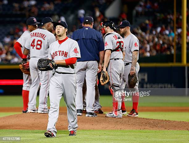 Pitcher Junichi Tazawa of the Boston Red Sox walks off the field during a pitching change while teammates convene on the mound in the seventh inning...