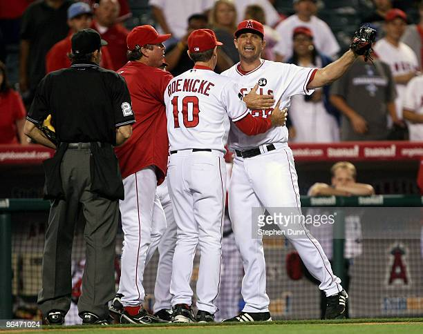 Pitcher Justin Speier of the Los Angeles Angels of Anaheim is restrained by coaches Ron Roenicke and Mickey Hatcher during a confrontation with home...