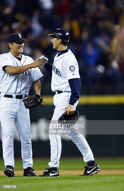Pitcher Kazuhiro Sasaki of the Seattle Mariners shakes hands with John Olerud after beating the Oakland Athletics at Safeco Field on April 14 2003 in...