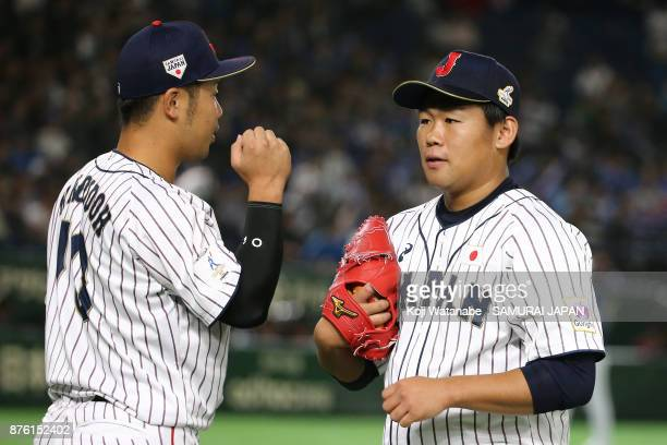 Pitcher Kazuto Taguchi of Japan is congratulated by his team mate Kensuke Kondo after the top of second inning during the Eneos Asia Professional...