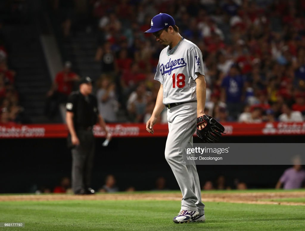 Pitcher Kenta Maeda #18 of the Los Angeles Dodgers hangs his head after being taken out of the game in the sixth inning during the MLB game against the Los Angeles Angels of Anaheim at Angel Stadium on July 6, 2018 in Anaheim, California.