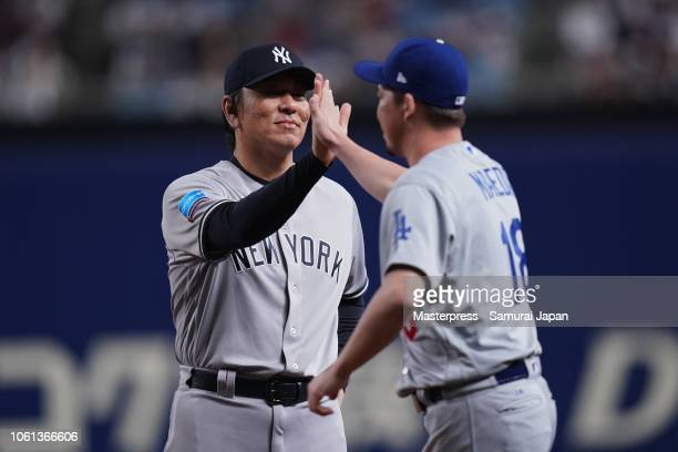 Pitcher Kenta Maeda of the Los Angeles Dodgers high fives with Coach Hideki Matsui of the New York Yankees as he is introduced prior to the game five...