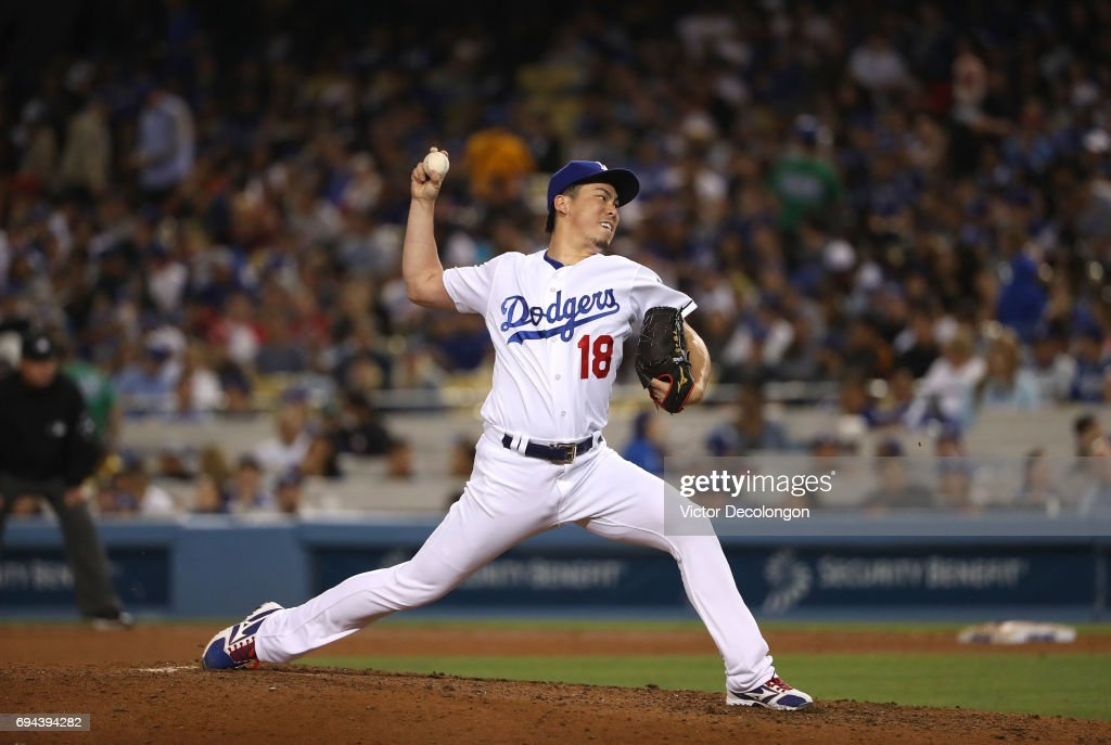 Pitcher Kenta Maeda #18 of the Los Angeles Dodgers pitches in relief in the sixth inning during the MLB game against the Cincinnati Reds at Dodger Stadium on June 9, 2017 in Los Angeles, California.