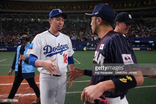 Pitcher Kenta Maeda of the Los Angeles Dodgers shakes hands with Infielder Ryosuke Kikuchi of Japan after the game six between Japan and MLB All...