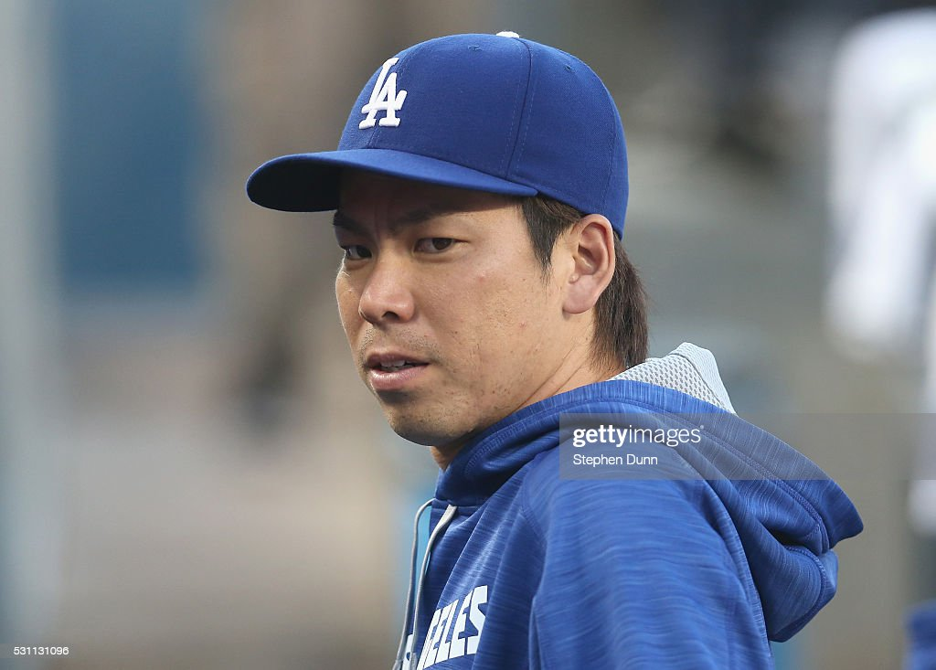 Pitcher Kenta Maieda #18 of the Los Angeles Dodgers stands in the dugout before the game with the New York Mets at Dodger Stadium on May 12, 2016 in Los Angeles, California.