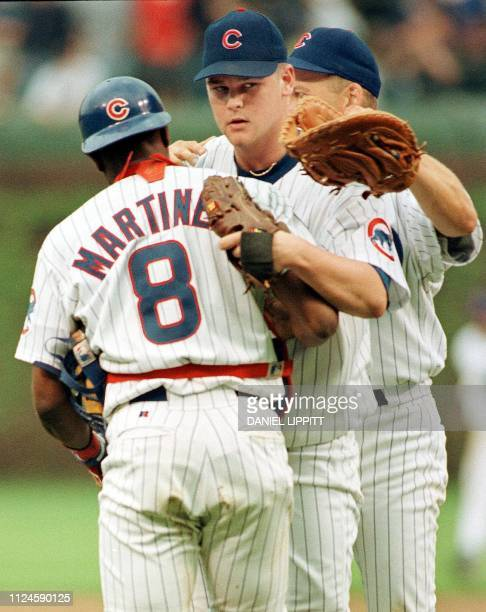 Pitcher Kerry Wood of the Chicago Cubs is hugged by teammates Sandy Martinez and Mark Grace after his game against the Houston Astros 06 May at...