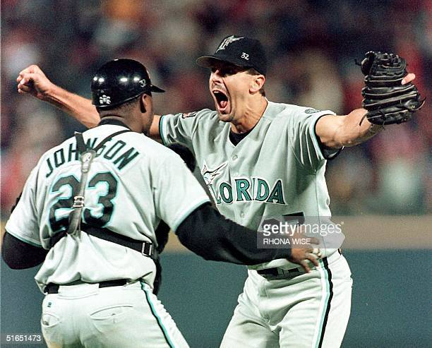 Pitcher Kevin Brown of the Florida Marlins runs to hug his catcher Charles Johnson after their team's 74 defeat of the Atlanta Braves 14 October in...