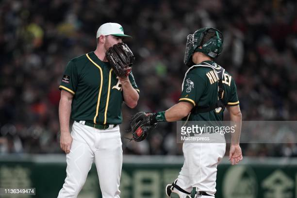 Pitcher Liam Hendriks of the Oakland Athletics talks with Catcher Nick Hundley in the bottom of 1st inning during the game between Hokkaido NipponHam...