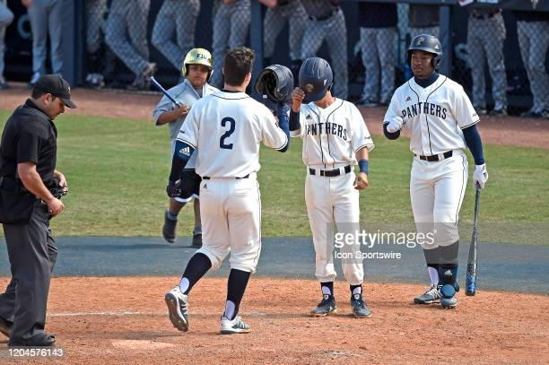 Pitcher Logan Allen celebrates his two-run home run in the bottom of the eighth inning with second baseman Derek Cartaya and outfielder Nathan Housen...