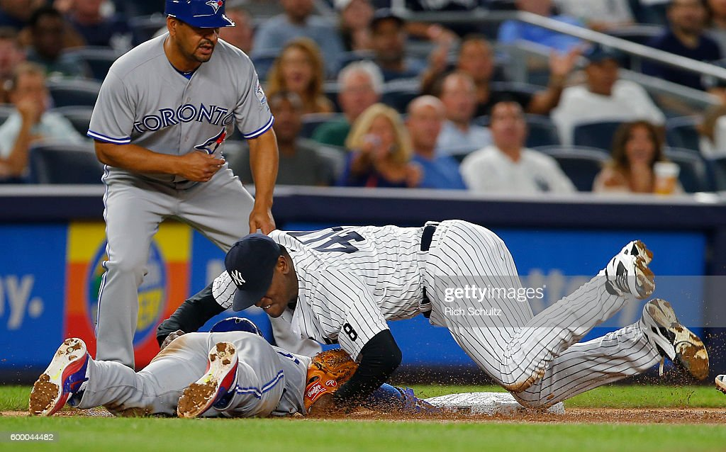 Pitcher Luis Severino #40 of the New York Yankees rolls over Devon Travis #29 of the Toronto Blue Jays after making the tag on a rundown play on a ball hit by Josh Donaldson #20 during the sixth inning of a game at Yankee Stadium on September 7, 2016 in the Bronx borough of New York City. The Yankees defeated the Bluejays 2-0.