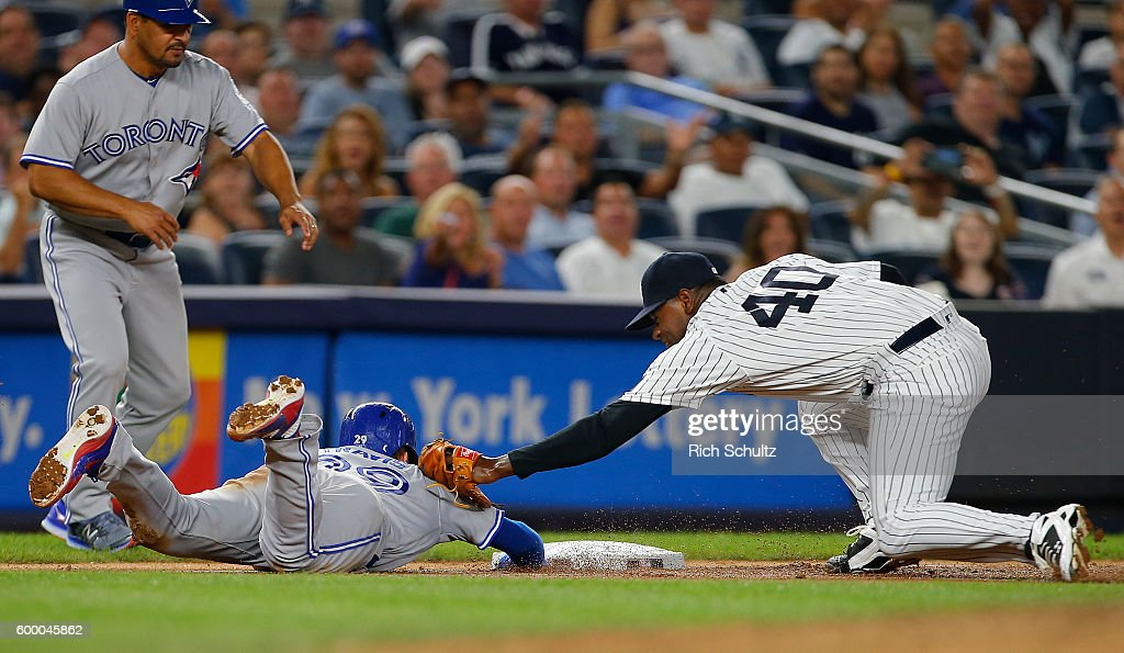 Pitcher Luis Severino #40 of the New York Yankees tags out Devon Travis #29 of the Toronto Blue Jays at the end of a rundown play on a ball hit by Josh Donaldson #20 during the sixth inning of a game at Yankee Stadium on September 7, 2016 in the Bronx borough of New York City. The Yankees defeated the Bluejays 2-0.