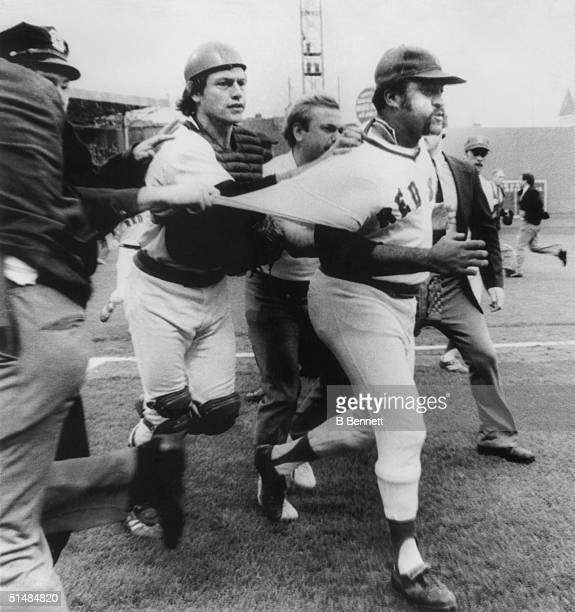 Pitcher Luis Tiant of the Boston Red Sox almost loses his shirt as he and teammate catcher Carlton Fisk get escorted off the field after defeating...