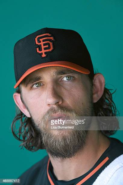 Pitcher Madison Bumgarner of the San Francisco Giants sits in the dugout before the game against the San Diego Padres during a spring training game...