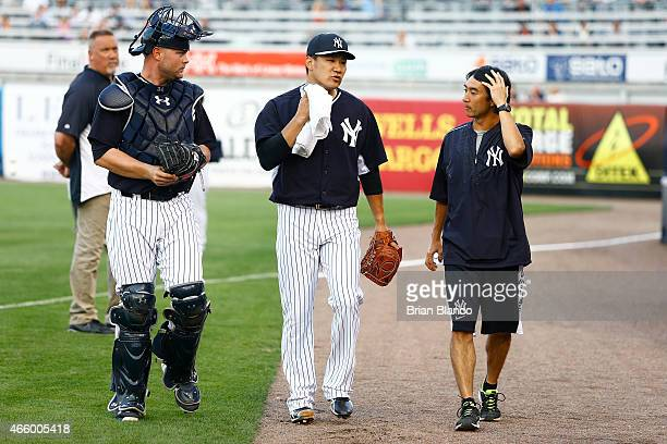 Pitcher Masahiro Tanaka of the New York Yankees and catcher Brian McCann walk out to the field before starting a spring training game against the...