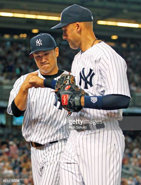 Pitcher Masahiro Tanaka of the New York Yankees gets a fist pump from teammate Derek Jeter after getting out of the eighth inning against the Boston...