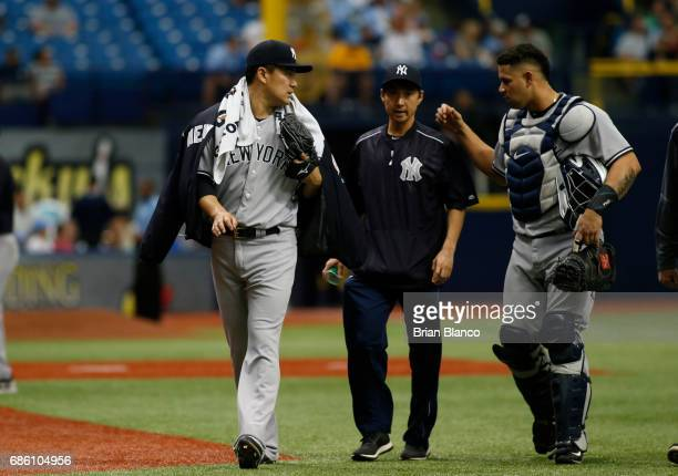 Pitcher Masahiro Tanaka of the New York Yankees speaks through his translator to catcher Gary Sanchez before the start of a game against the Tampa...