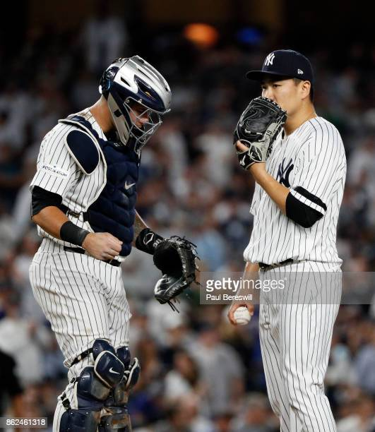 Pitcher Masahiro Tanaka of the New York Yankees talks with catcher Gary Sanchez on the mound in game 3 of the American League division series MLB...
