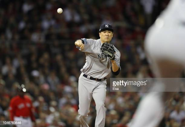 Pitcher Masahiro Tanaka of the New York Yankees throws to first base in an attempt to pick off Jackie Bradley Jr #19 of the Boston Red Sox during the...
