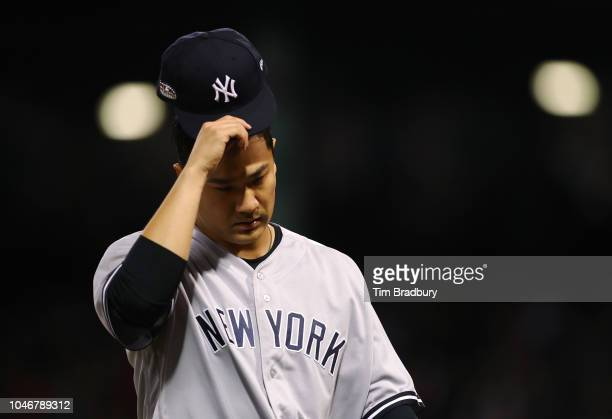 Pitcher Masahiro Tanaka of the New York Yankees tips his cap as he walks back to the dugout after the fourth inning of Game Two of the American...