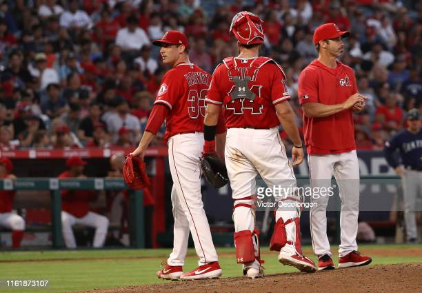 Pitcher Matt Harvey of the Los Angeles Angels of Anaheim leaves the game after handing the ball to manager Brad Ausmus as catcher Kevan Smith looks...