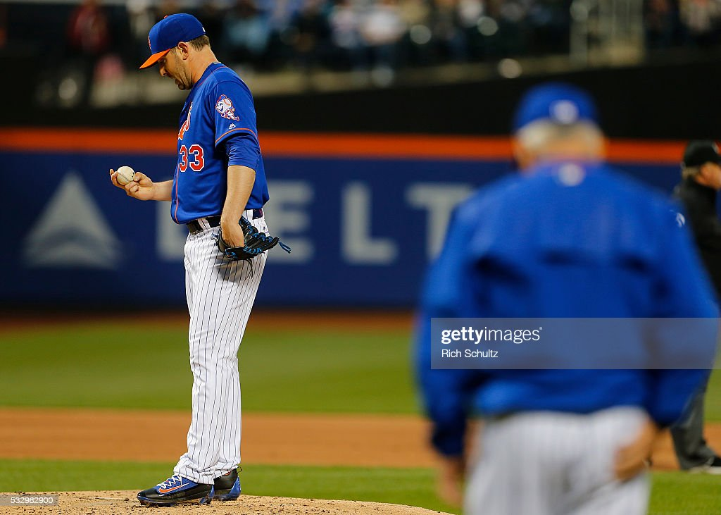 Pitcher Matt Harvey #33 of the New York Mets stares at the ball as manager Terry Collins #10 comes out to relieve him during the third inning against the Washington Nationals at Citi Field on May 19, 2016 in the Flushing neighborhood of the Queens borough of New York City.
