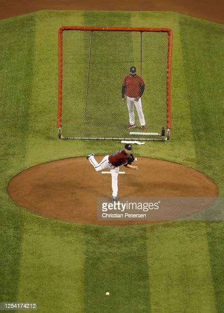 Pitcher Merrill Kelly of the Arizona Diamondbacks throws a pitch as he participates in summer workouts ahead of the abbreviated MLB season at Chase...